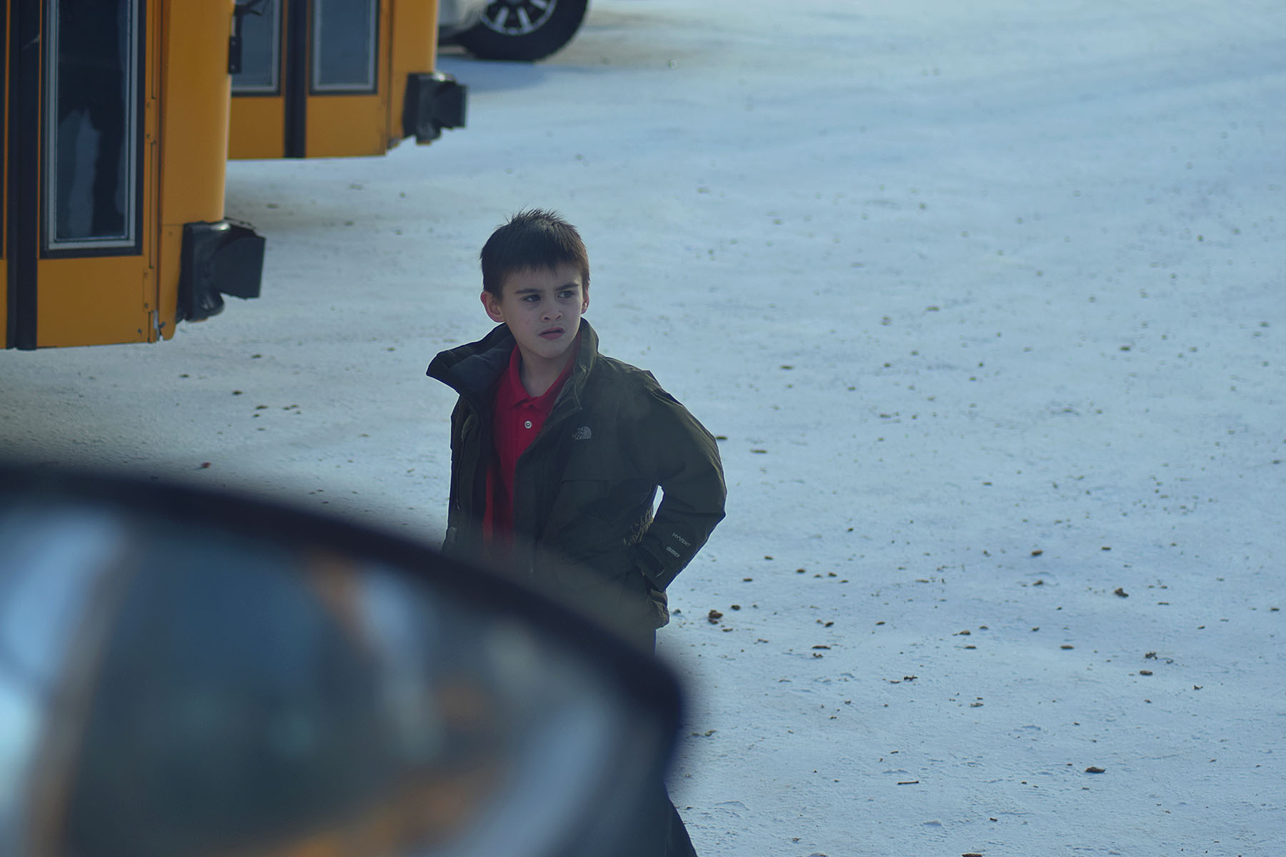 A little boy looking for his bus.